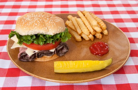 one large roast beef sandwich with fries and a pickle spear on traditional red and white checkered tablecloth