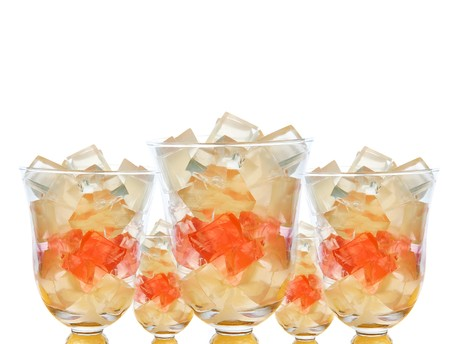many bowls of fruit lemonade gelatin cubes with whipped cream over white photo