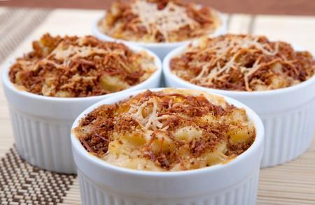 macarrones: cuatro cuencos ramekin de cena casera de macarrones y queso rematado con corteza marrón de caseoso tostado  Foto de archivo