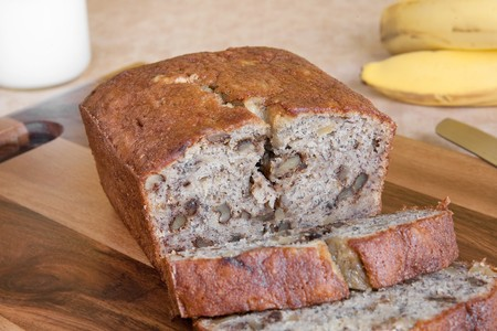 sliced loaf of walnut banana bread with bananas and milk in the background