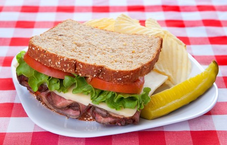 roast beef and cheese sandwich with lettuce, tomato and pickle on a classic red and white checkered background