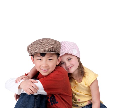 girl in a hat: two cute little diverse sibling children hugging and smiling against a white background