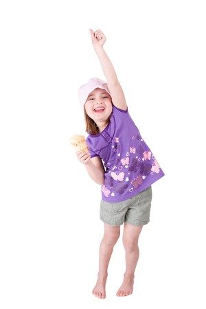 one very happy young girl child celebrating with her arm up and ice cream smiling happily Foto de archivo