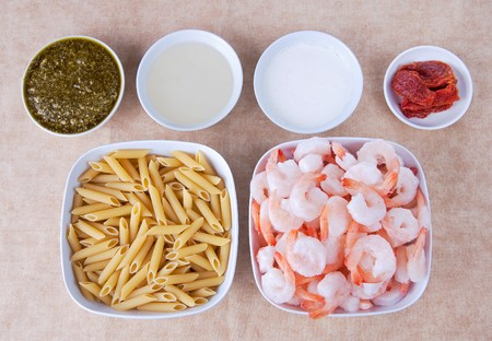 en: mise en place setup of ingredients for shrimp pesto over penne with sundried tomato