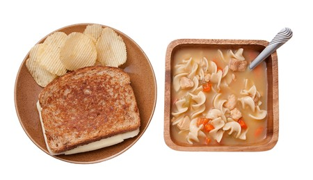 one grilled cheese sandwich with plain chips and a bowl of chicken noodle soup. traditional homestyle food on rustic dishes photo