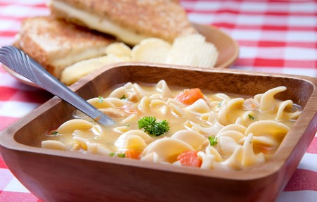 meat soup: one bowl of chicken noodle soup and a grilled cheese sandwich background on classic red and white checkered background Stock Photo
