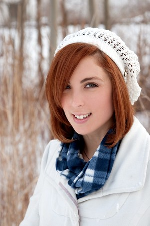 one redhead young adult woman in a warm coat and hat in a winter scene photo