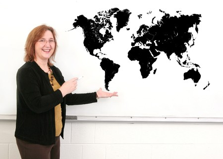 a middle aged woman teacher showing a black map on the whiteboard photo