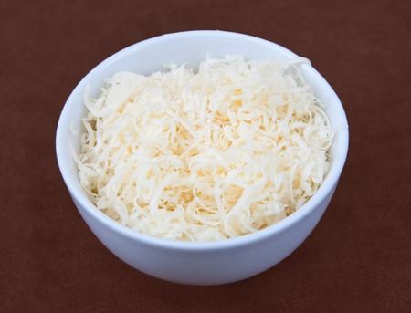 queso rayado: un peque�o blanco prep cuenco lleno de queso rallado listo para cocinar.