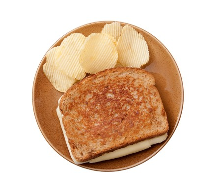 grilled cheese sandwich on a plate with chips isolated over white photo