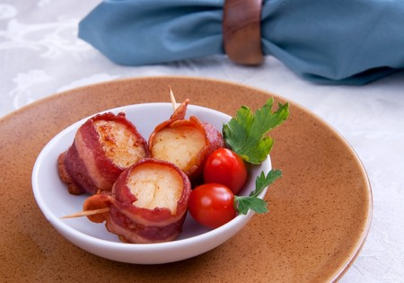 three bacon wrapped scallops in a bowl with tomatos Foto de archivo