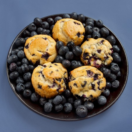 big plate of blueberry muffins surrounded by blueberries on blue photo