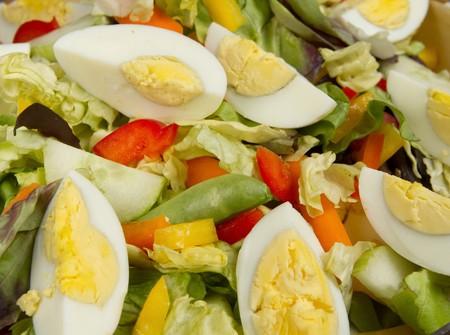 quartered egg in a green salad closeup photo