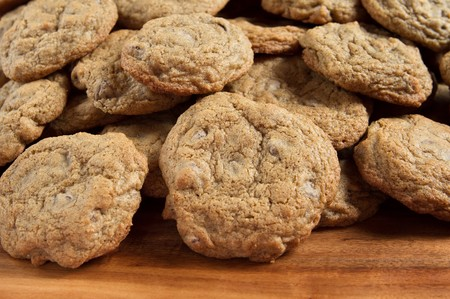 large stack of gluten free chocolate chip cookies on a cutting board Foto de archivo