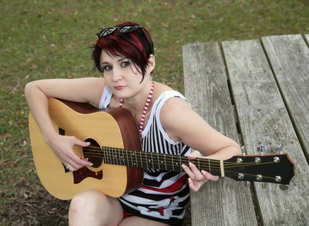 musically: one adult woman playing guitar in a park on a picnic table Stock Photo