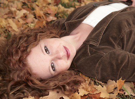 closeup portrait of one vibrant red haired woman happy and smiling outdoors photo
