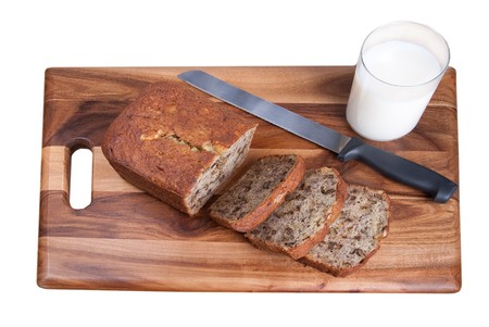 sliced loaf of banana walnut bread on a wooden cutting board with a glass of milk over white photo