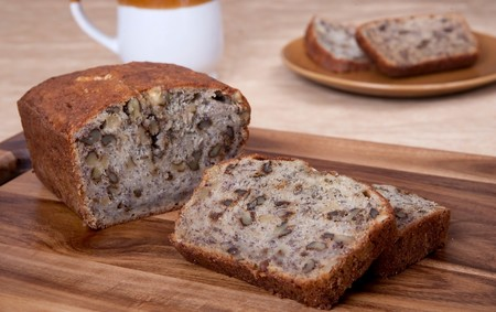 loaves: sliced loaf of banana walnut bread on a cutting board with one serving of two slices and a mug in the background