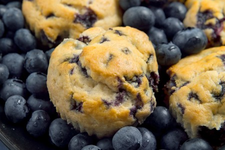 small stack of blueberry muffins and fresh blueberries over a blue background closeup Banque d'images
