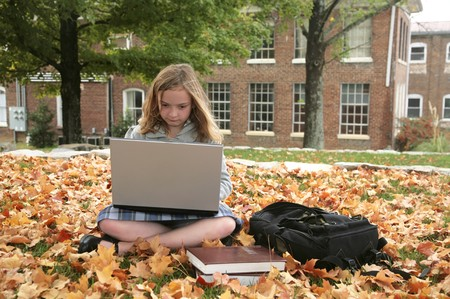 one young grade school student studying outdoors on a laptop in autumn photo