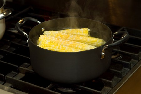 boiling: pot of boiling water and many ears of corn cooking Stock Photo