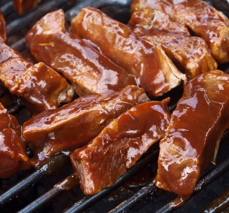 barbecue beef spare ribs cooking on a grill outdoors in summer photo