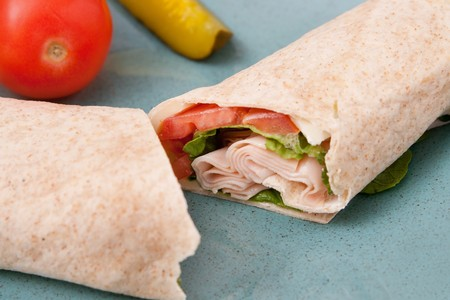 one cut turkey, tomato and lettuce wrap sandwich photo