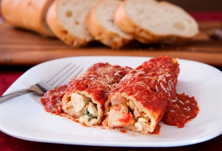 two tasty stuffed manicotti shells topped with pasta sauce and Italian bread on the side