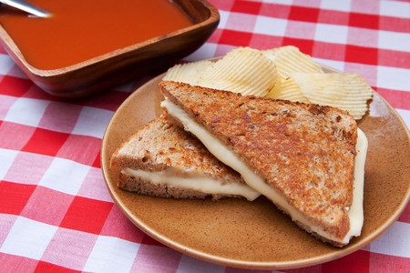basic grilled cheese sandwich on toasted bread with chips and a big bowl of tomato soup on a traditional checkered red and white tablecloth photo