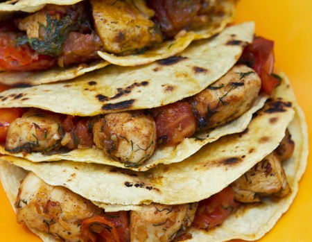 chicken tacos full with tomato and herbs on a yellow plate