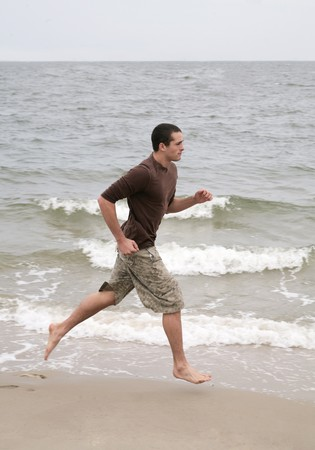 one twenties young fit man running along the beach photo