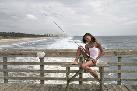 African American twenties woman with a fishing pole at Myrtle Beach pier photo