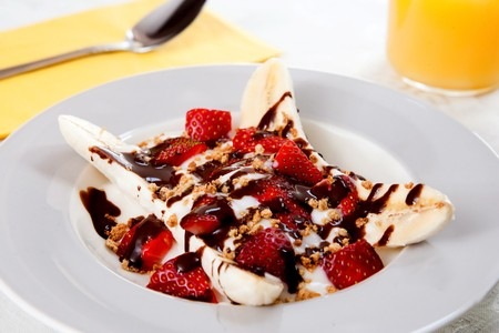 one healthy plate of banana split with yogurt, strawberries and low fat hot fudge topping photo