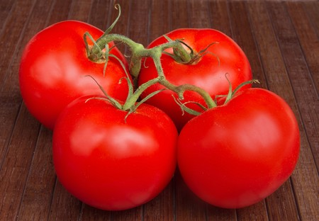 four vine ripe tomatoes on a brown wooden mat Stock Photo - 7969536