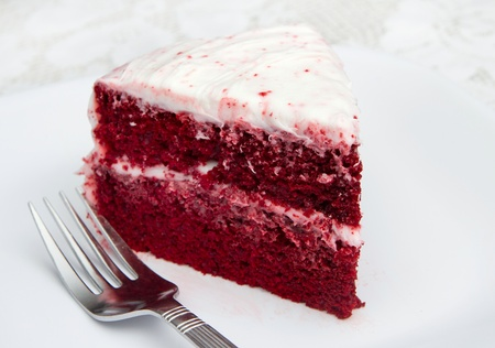 one slice of red velvet cake on a white plate with a fork Foto de archivo