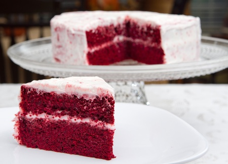 red velvet cake on a glass platter with one slice removed in front Stock Photo