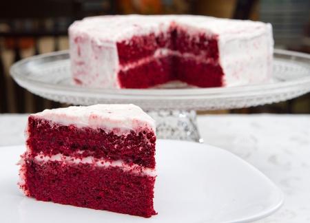 velvet background: red velvet cake on a glass platter with one slice removed in front Stock Photo