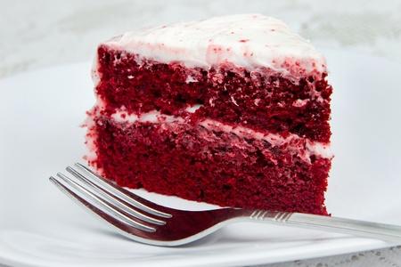 velvet background: one slice of red velvet cake with a fork on a white plate Stock Photo