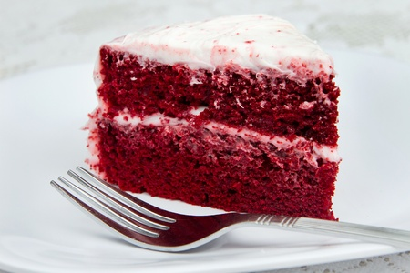 one slice of red velvet cake with a fork on a white plate Foto de archivo