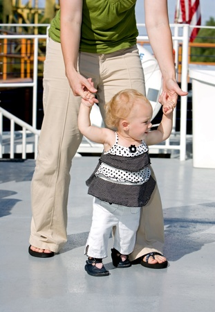 one young girl holding her moms hand while walking on a cruise ship Banco de Imagens