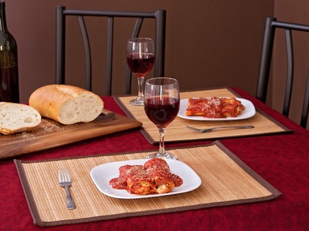 two portions of chicken manicotti with wine and bread photo