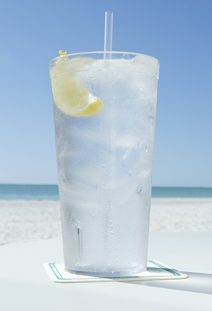 one cold glass of ice water with lemon on the beach in summer