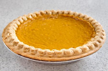 one whole pumpkin pie on a kitchen counter photo
