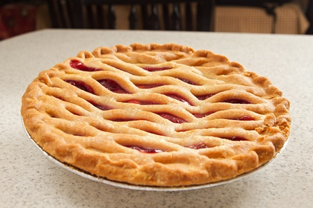 one whole cherry pie in a kitchen on the counter photo