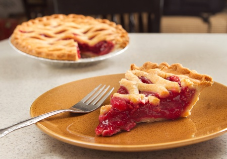 cherry pie: one slice of cherry pie ready to eat with a fork taken from the whole