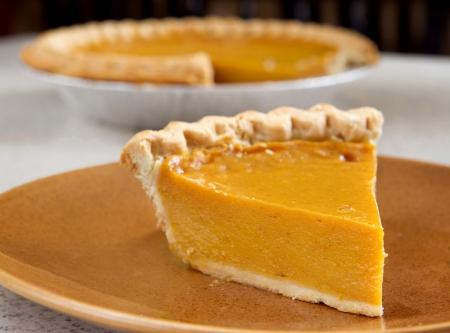 Ein Slice der Kürbis-Kuchen aus der gesamten schneiden Standard-Bild - 8798605
