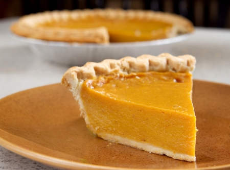 one slice of pumpkin pie cut from the whole Stock Photo - 8798605