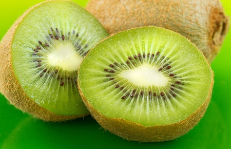 sliced kiwifruit closeup on a green plate photo