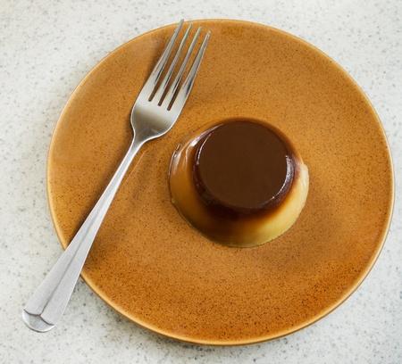 one small caramel flan dessert on a plate