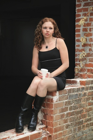 one redhead twenties woman alone with her coffee in an urban environment Banque d'images